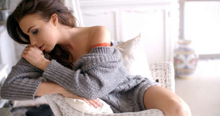 Seductive Woman in Cardigan Touching her Hair Stock Photo