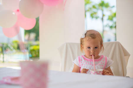 tomando jugo: Little Toddler Girl Drinking Juice From Paper Cup with Straw  She Sitting on Terrace During Her Birthday Party