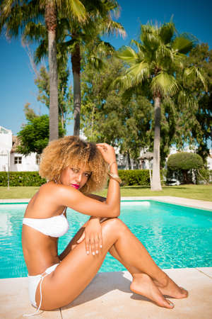 bikini pool: Sexy Model with Afro Haircut Posing Next to Exotic Swimming Pool  She Wearing White Skimpy Bikini Stock Photo