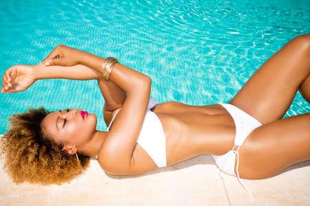models posing: Sensual ni�a de raza mixta se relaja en Piscina al aire libre Foto de archivo