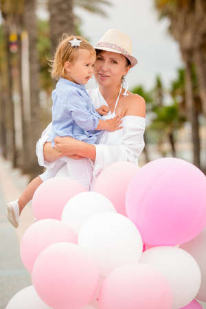 childs birthday party: Trendy mother with a baby daughter at a childs outdoor birthday party with pink and white balloons  tropical seaside setting Stock Photo