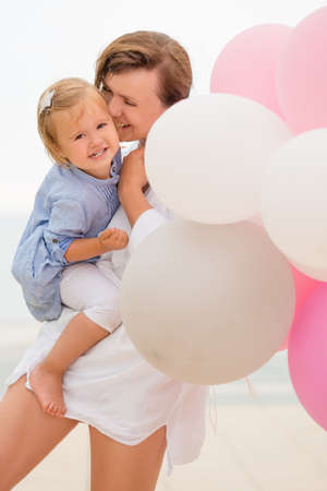 happy moment: Loving mother and her small daughter share a tender happy moment as she holds the toddler in her arms with a bunch of pink and white party balloons.