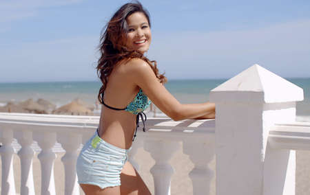 brunette girl: Smiling attractive woman in a sexy summer outfit standing leaning on the balustrade of a beachfront promenade looking back at the camera
