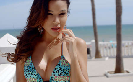 busty: Thoughtful busty young woman at the seaside standing in her bikini looking at the camera  close up head and shoulders showing off her cleavage