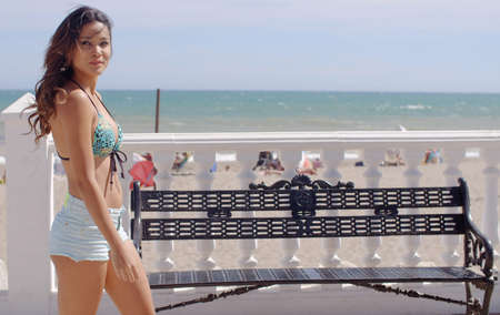 Sexy young woman strolling along a promenade overlooking a tropical beach and ocean turning to look at the camera with a seductive smile  with copyspace