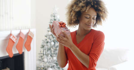 blissful: Blissful happy young woman holding up a Christmas gift in her hands as she tries to guess the contents in her decorated living room with tree.