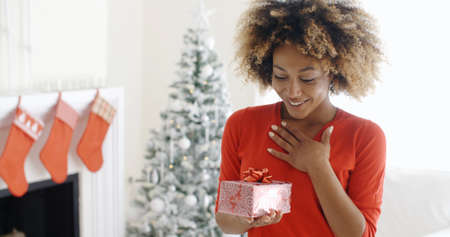woman chest: Excited young woman with an unexpected Christmas gift holding her hand to her chest with a look of surprise  decorated Christmas tree and fireplace behind
