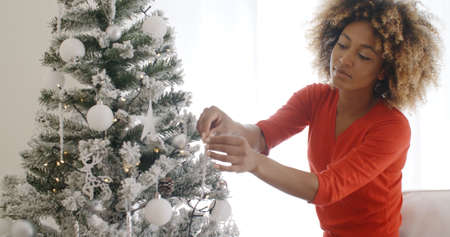afro hairdo: Attractive African woman with a wild curly afro hairdo decorating the Christmas tree with tinsel and ornaments to celebrate the festive season