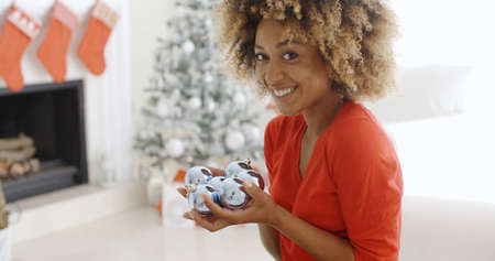 young add: Young woman carrying a handful of Xmas decorations looking at the camera with a happy friendly smile as she prepares to add them to the ornaments on the Christmas tree in her living room.