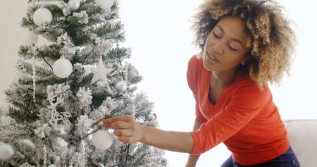 adds: Pretty young African woman decorating her Christmas tree adding the last touches to the decorations as she adds a white star