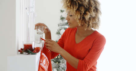 mantelpiece: Happy young African American woman hanging colorful red Christmas stockings on the mantelpiece of her fireplace to celebrate the festive season