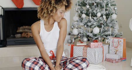 eyeing: Young woman enjoying Christmas sitting cross-legged on the floor in front of the decorated tree eyeing the pile of decorative gift-wrapped  presents with a beaming smile.