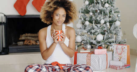 christmas woman: Blissful young woman holding a mug of hot coffee with a beaming smile of pleasure as she sits cross-legged in front of the Christmas tree.