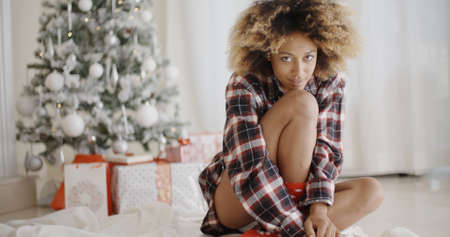 femmes souriantes: Thoughtful trendy young African woman sitting on the floor in front of a decorated Christmas tree at home looking at the camera