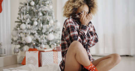 snuggling: Trendy young African woman waiting for Christmas sitting cross-legged on the floor in front of the decorated tree snuggling into her warm jacket