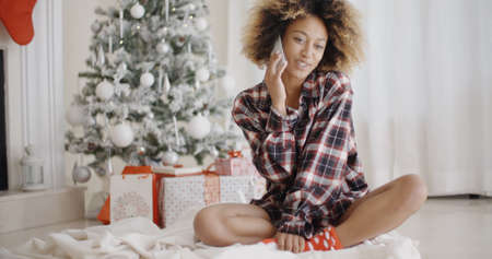 socialising: Young African woman in a trendy outfit sitting on the floor relaxing in front of the Christmas tree chatting on her mobile phone Stock Photo