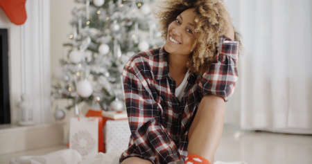 charisma: Thoughtful trendy young African woman sitting on the floor in front of a decorated Christmas tree at home looking at the camera