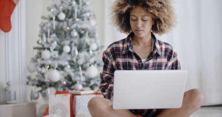 trabajando en casa: Estudiante africano joven que trabaja en su computadora portátil en frente del árbol de Navidad decorado en su sala de estar en casa