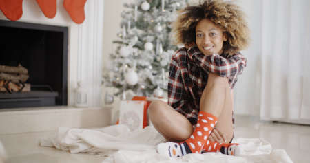 crosslegged: Smiling young woman in a Christmas living room sitting cross-legged in front of the tree alongside a decorated fireplace