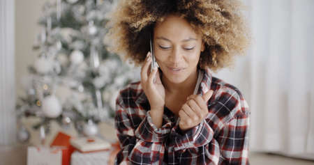 socialising: Attractive young African girl chatting on her mobile phone in front of the Christmas tree at home  natural pose