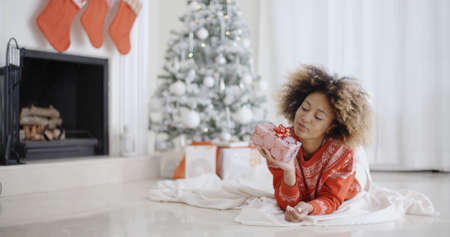 longing: Young African girl lying on a rug in front of the Christmas tree looking at her Xmas gift with a look of anticipation and longing