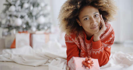 front room: Thoughtful attractive young African woman with a Christmas gift lying on the floor in the living room in front of the decorated tree