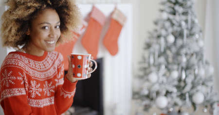 Pretty smiling young African woman in a festive red sweater drinking a mug of Christmas coffee in front of the Christmas tree at home Stock Photo