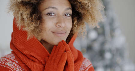 cold woman: Cute young African woman in winter fashion wearing a festive red sweater and gloves posing in front of a decorated Christmas tree