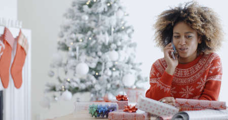 preoccupied: Young African woman wrapping gifts at Christmas sitting at a table in front of the Xmas tree chatting on her mobile phone  natural pre-occupied pose.