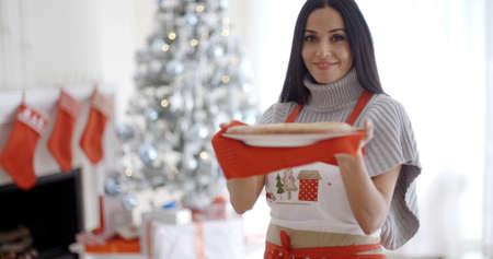 mandil: Mujer joven para hornear dulces de navidad de pie en su delantal festivo delante del árbol que sostiene una tarta recién horneado