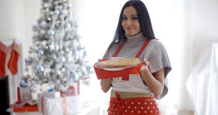 olfato: Mujer joven para hornear dulces de navidad de pie en su delantal festivo delante del árbol que sostiene una tarta recién horneado