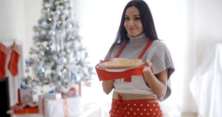 woman baking: Young woman baking Christmas treats standing in her festive apron in front of the tree holding a freshly baked tart Stock Photo