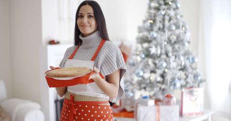 mandil: Risa sonriente joven cocinero de Navidad en un delantal rojo festivo que sostiene una tarta recién horneado en sus manos delante del árbol de Navidad