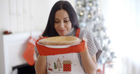 woman baking: Attractive young woman baking tarts for Xmas standing in front of the Christmas tree savoring the aroma of a freshly baked pie