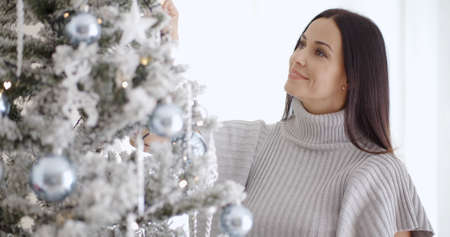 femmes souriantes: Pretty young woman with long brown hair standing decorating her white and silver themed Christmas tree with a smile of pleasure Banque d'images