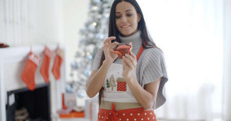 Pretty young woman enjoying her Christmas baking standing in front of the Xmas tree in a festive apron preparing to eat a freshly baked cookie