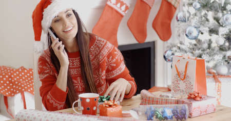 on call: Young woman in a festive red Santa hat and sweater making a Christmas greeting call on her mobile phone listening to the conversation with a happy smile. Stock Photo