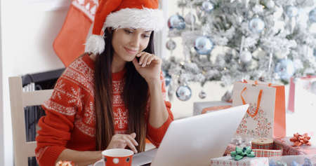 bargains: Smiling young woman surfing the internet on her laptop computer for Christmas bargains as she sits at a table in front of the decorated tree in her red Santa hat.