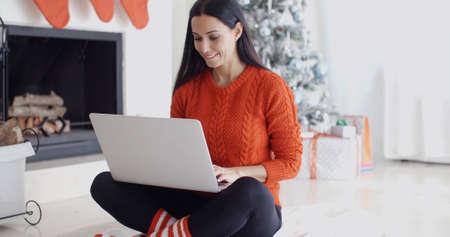 mujeres trabajando: Mujer joven descansando en su casa durante la Navidad se sienta con las piernas cruzadas en el suelo en la sala de estar delante del árbol de Navidad, navegar por internet en su ordenador portátil.