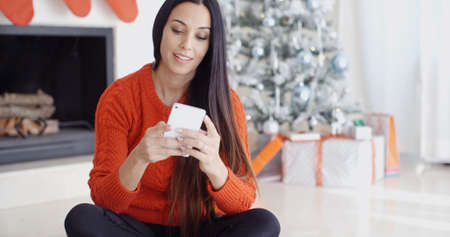 handphone: Young woman checking out her text messages on her mobile phone as she sits cross-legged on the floor in front of the Christmas tree at home.