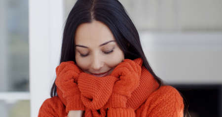 woollen: Serious attractive young woman in winter fashion standing with her gloved hands to her face as she snuggles down inside her warm woollen sweater and scarf.