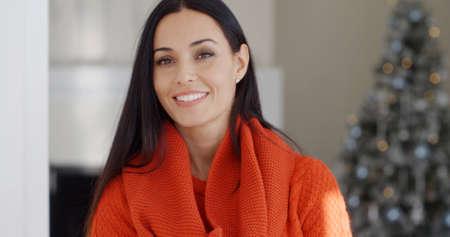 Sonriente mujer morena joven hermosa en la moda de invierno de pie en el interior en casa mirando a la cámara con una sonrisa feliz y amistosa