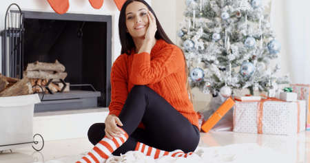 young tree: Trendy gorgeous young woman relaxing at Xmas sitting on a rug on the floor in front of the Christmas tree grinning at the camera Stock Photo