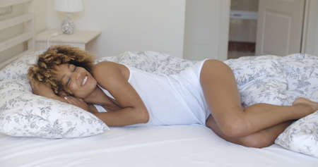 sexy woman on bed: Portrait of young beautiful african american woman flirting on bed