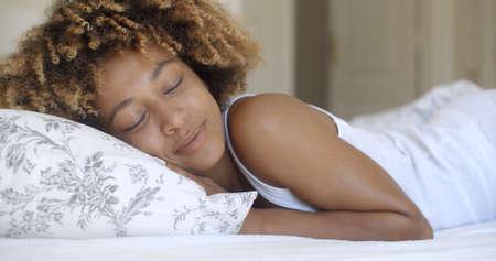 mujer en la cama: Joven mujer afroamericana atractiva despierta en su dormitorio Foto de archivo