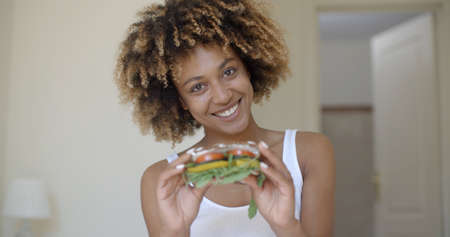 adult sandwich: Young african american woman sits in bed and holding in hands healthy sandwich Stock Photo