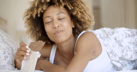 niña comiendo: Lindo joven mujer comiendo chocolate afroamericano en la cama en su casa Foto de archivo