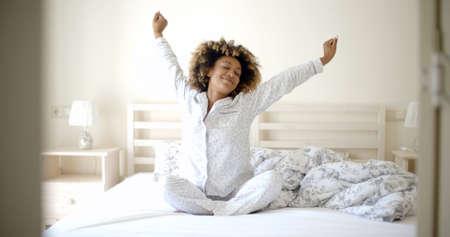집에서 침대에서 아침에 깨어 난 행복 젊은 여자