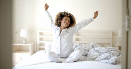 Happy young woman waking up in the morning in bed at home