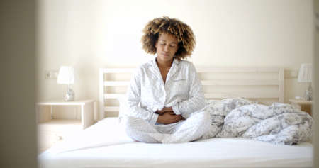 ache: Sick woman having a stomachache in her bedroom Stock Photo